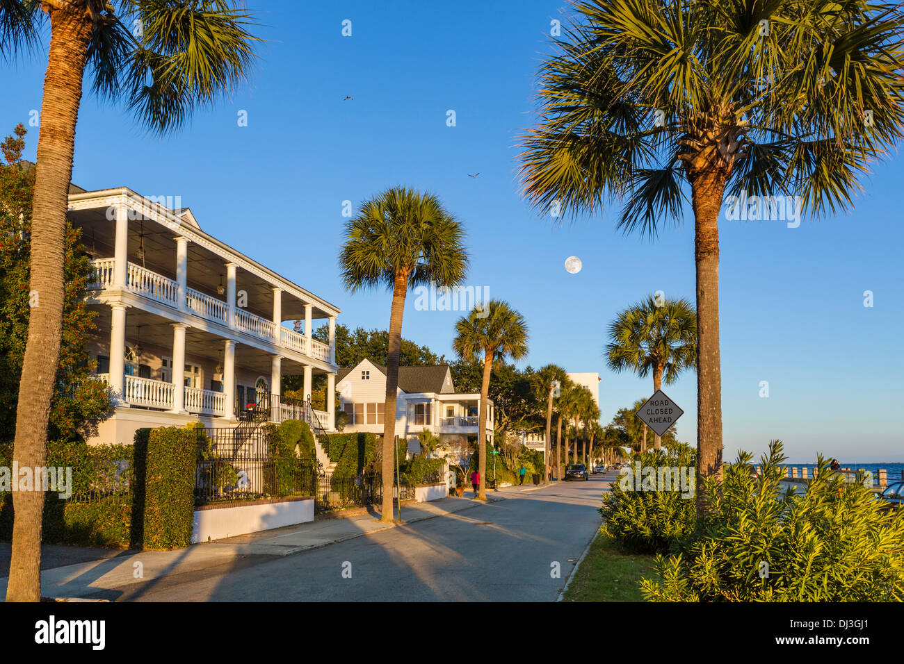 Historic houses along waterfront on Murray Boulevard, lit by setting sun, and with full moon, Charleston, South Carolina, USA - Stock Image