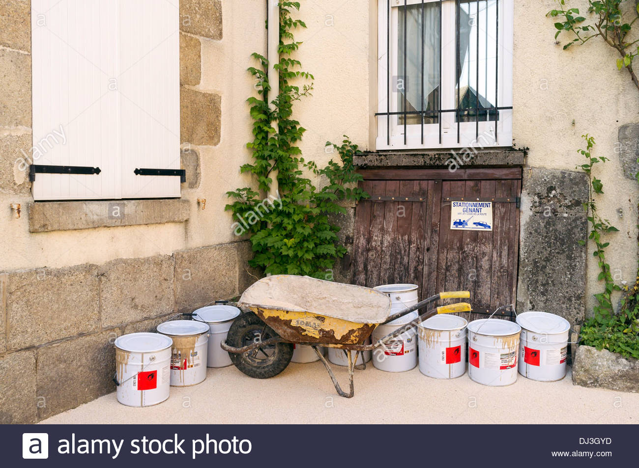 Wheelbarrow and paint buckets outside of a home being renovated, La Souterraine, La Creuse, Limousin, France - Stock Image