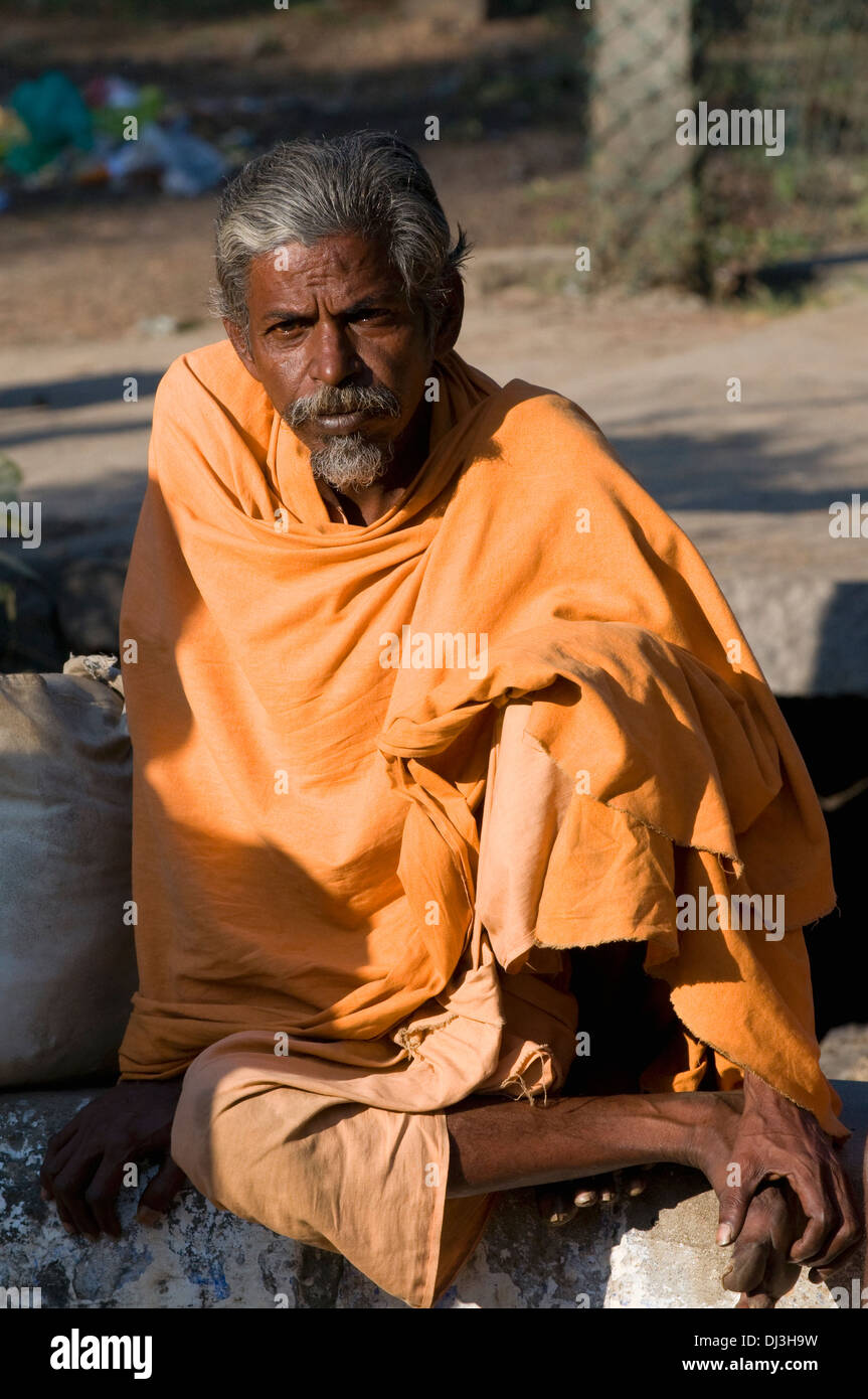 Sadhu, Indian holy man and renunciant sits relaxing in the morning sun - Stock Image