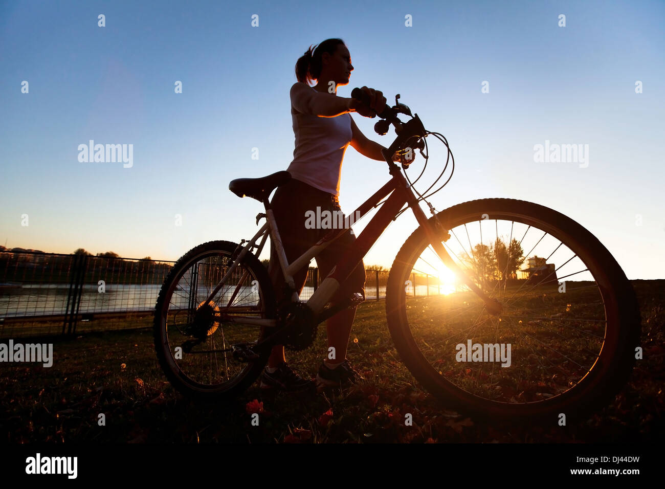 silhouette of young woman with bicycle outdoor - Stock Image