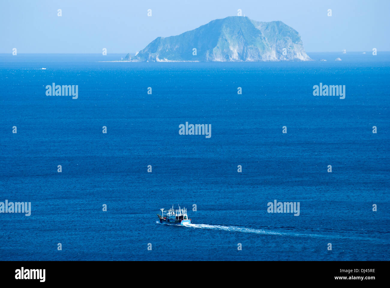Little fisher boat goes through island - Stock Image