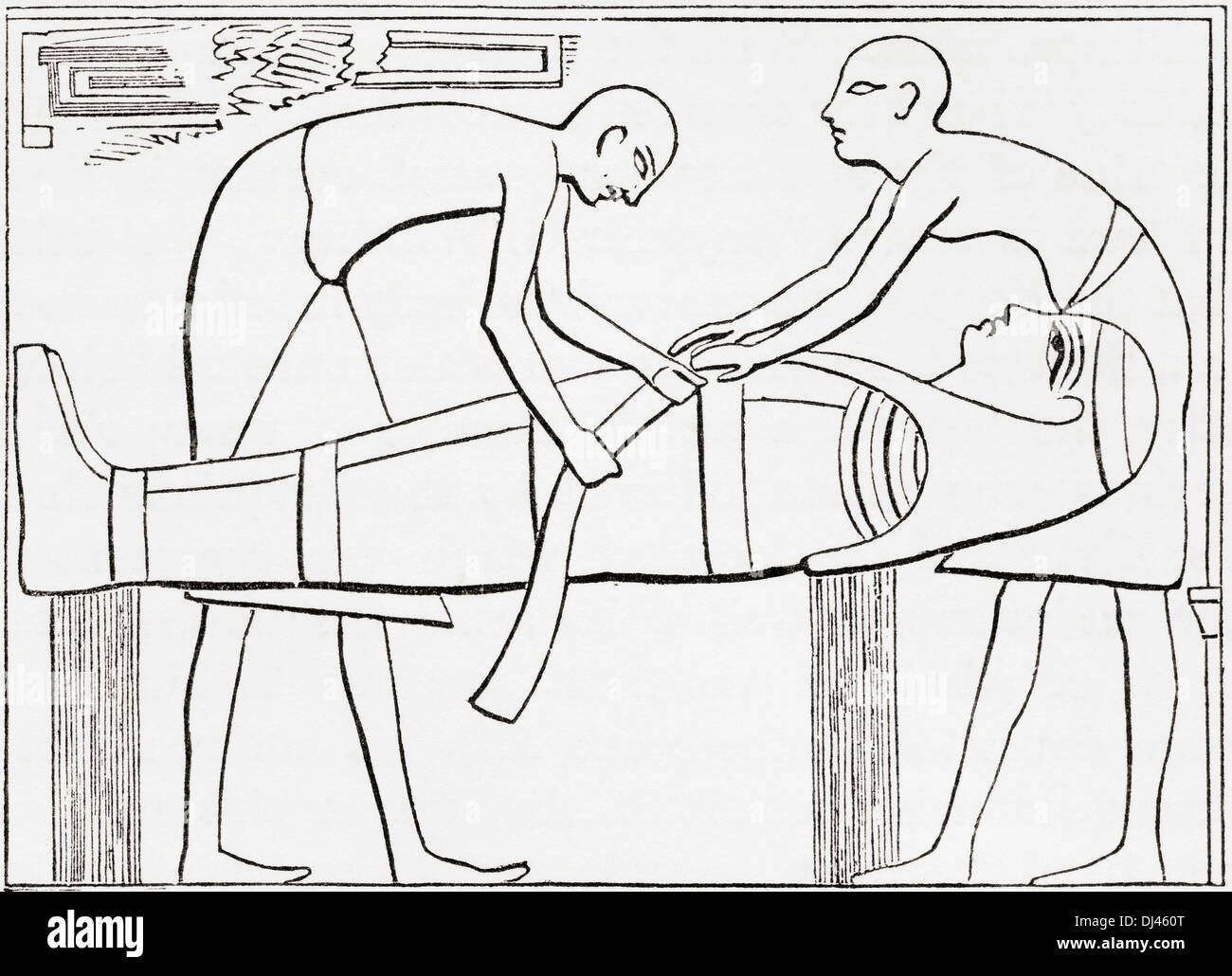 Ancient Egyptians swathing or wrapping bandages round a mummy. - Stock Image