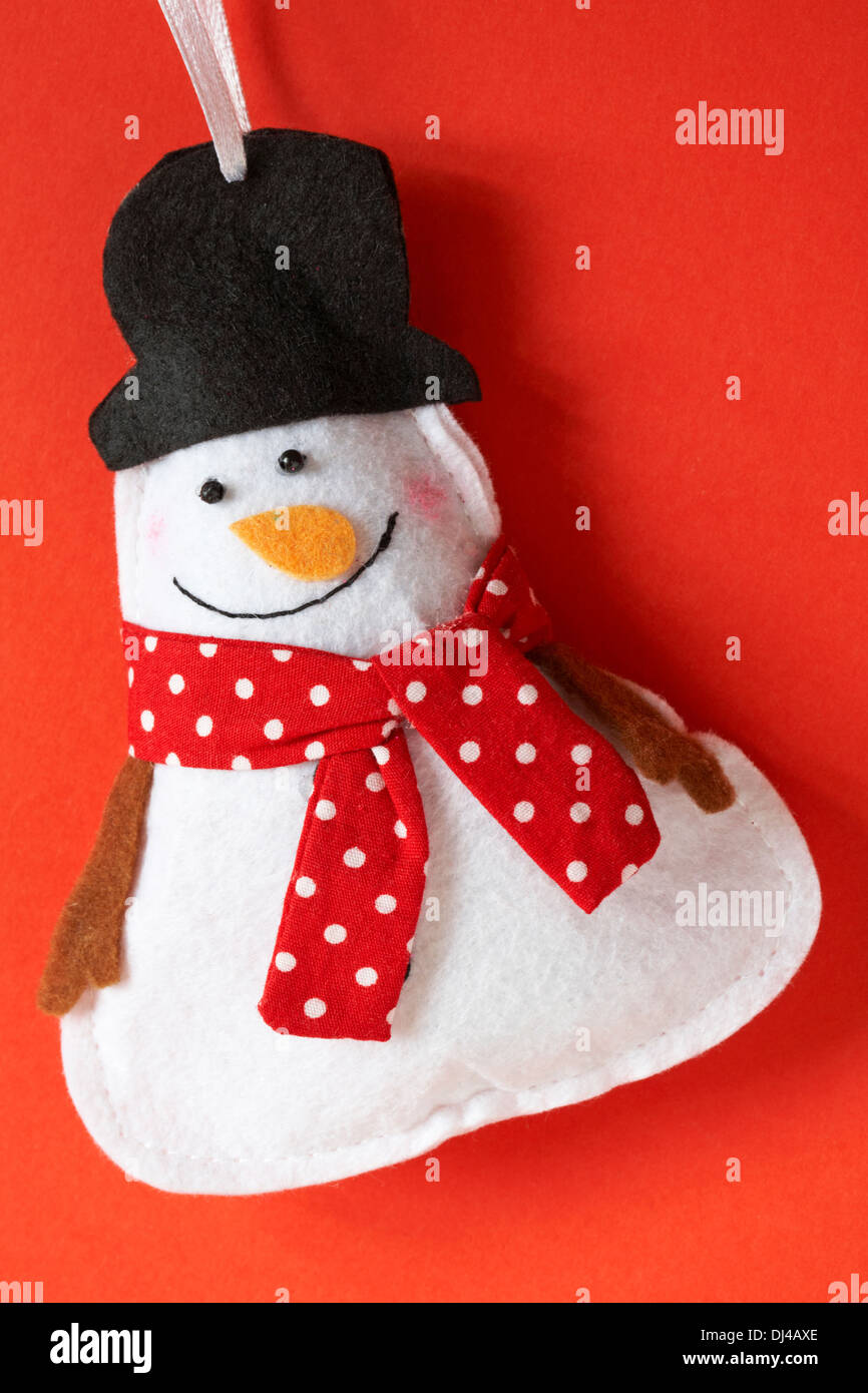 Snowman wearing red polka dot scarf and black top hat decoration ready for Christmas set on red background Stock Photo