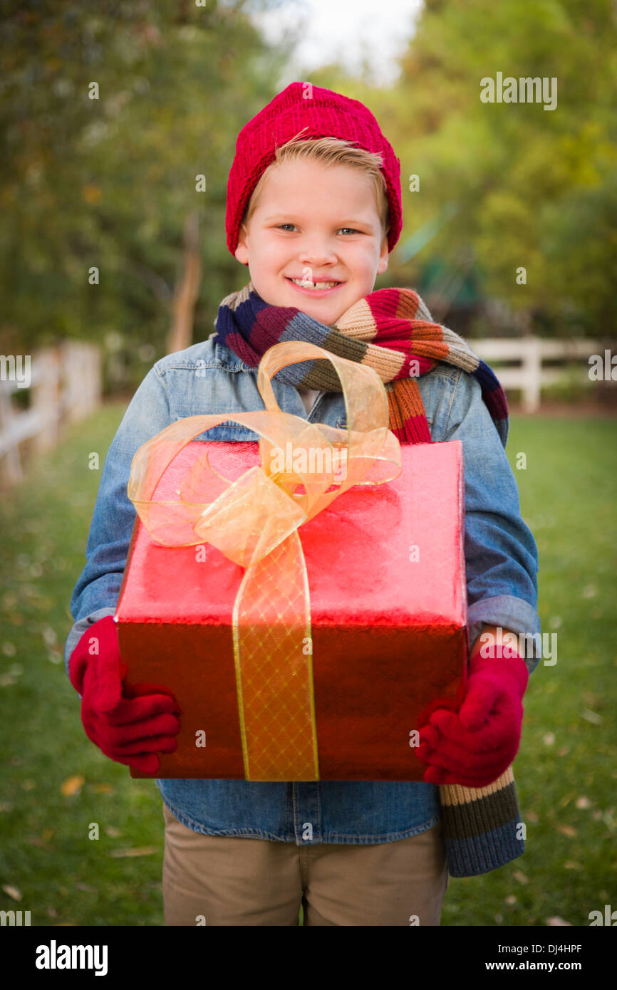 Handsome Young Boy Wearing Holiday Clothing Holding Christmas Gift Outside. - Stock Image