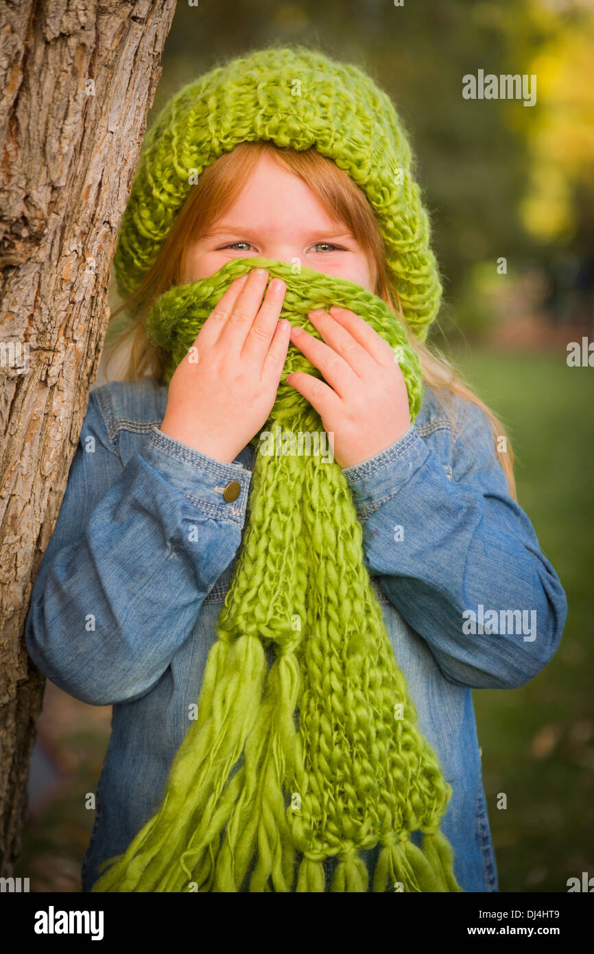 Cute Smiling Young Girl Wearing Green Scarf and Hat Posing for a Portrait Outside. - Stock Image