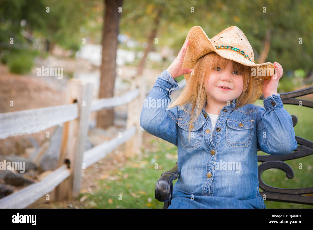 Cute Smiling Young Girl Wearing Cowboy Hat Posing for a Portrait Outside. - Stock Image