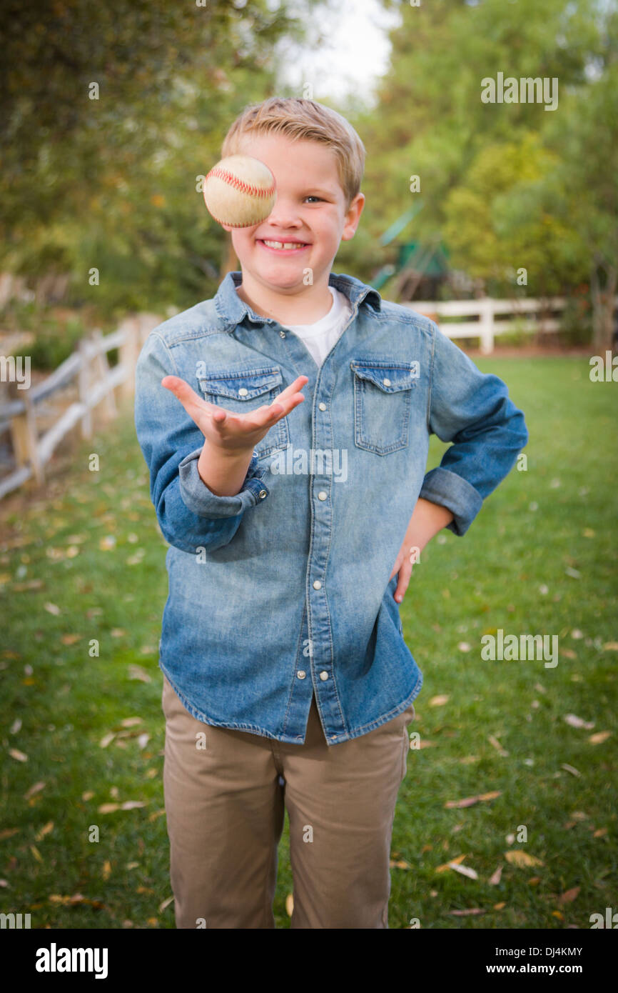 Handsome Young Boy Tossing Up His Baseball in the Park. - Stock Image