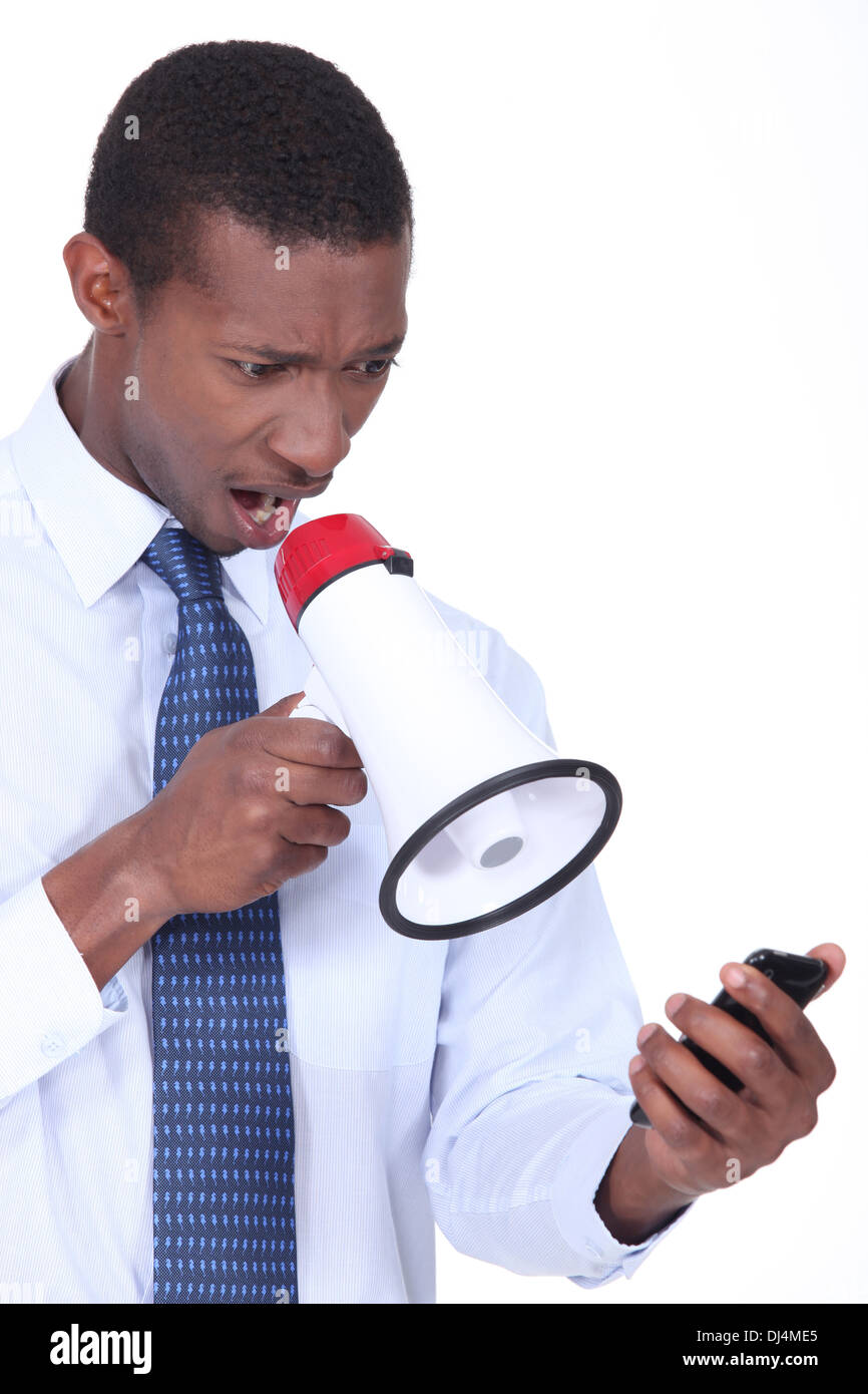 Annoyed man using a loudspeaker to shout at his cellphone - Stock Image