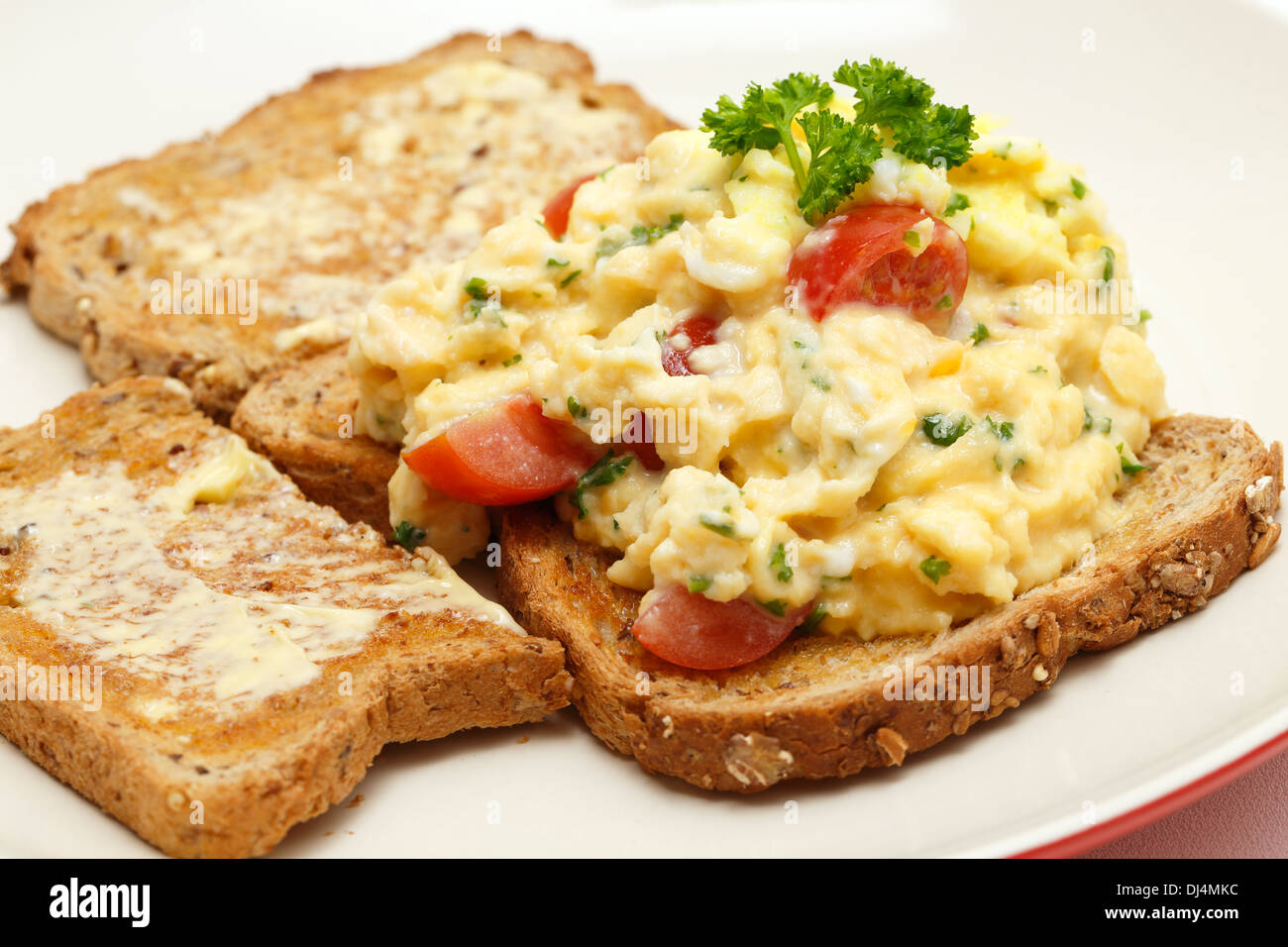 Scrambled Egg On Whole Grain Toast With Parsley And Cherry Tomatoes