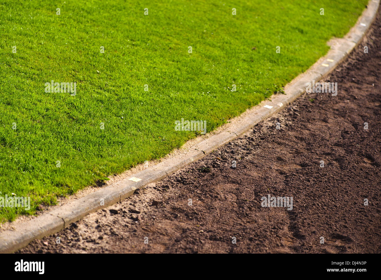 Curve of a pitch with grass and sand track - Stock Image