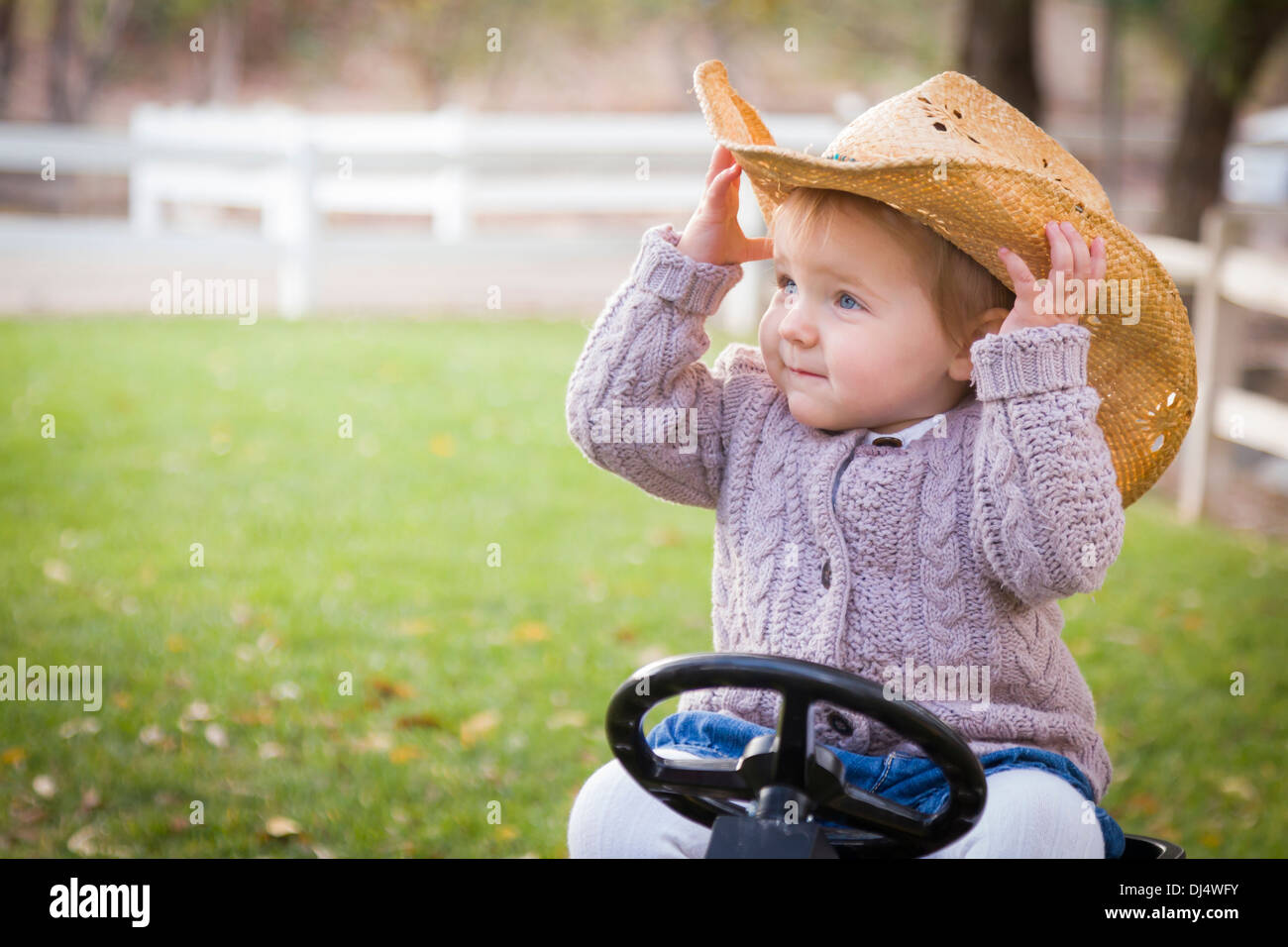 05a90840a5e1b Happy Young Toddler Wearing Cowboy Hat and Playing on Toy Tractor Outside.  - Stock Image