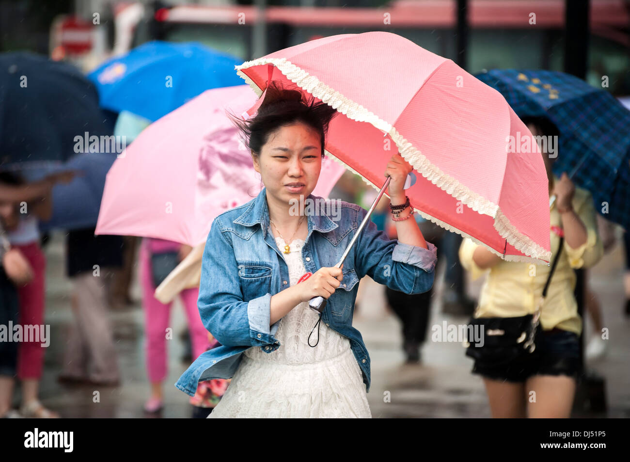 A girl carrying an umbrella during a tropical storm in Hong Kong Stock Photo