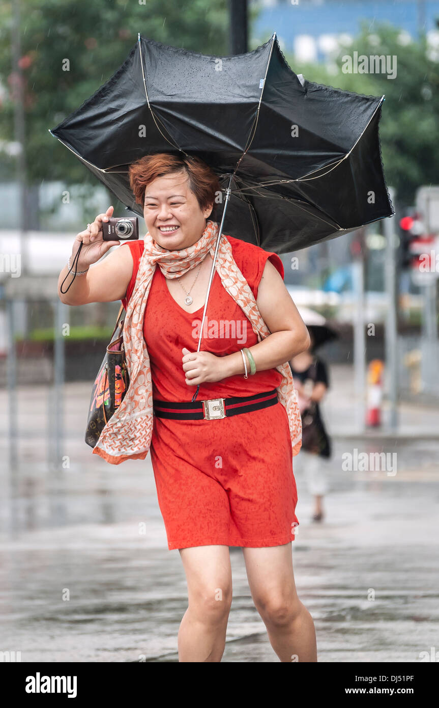 Chinese tourist with a broken umbrella takes photos during a tropical storm in Hong Kong - Stock Image