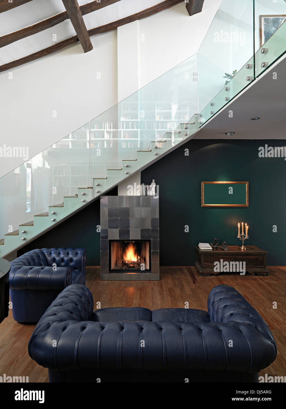 modern living room in the attic with fireplace, wood floor and staircase - Stock Image