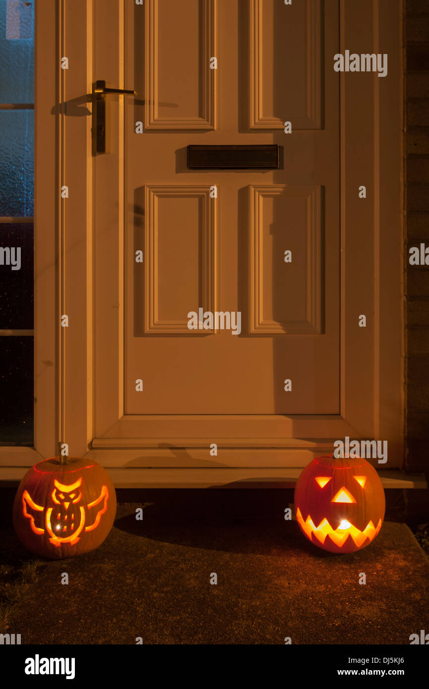 Halloween carved pumpkins outside a house door in the Uk - Stock Image