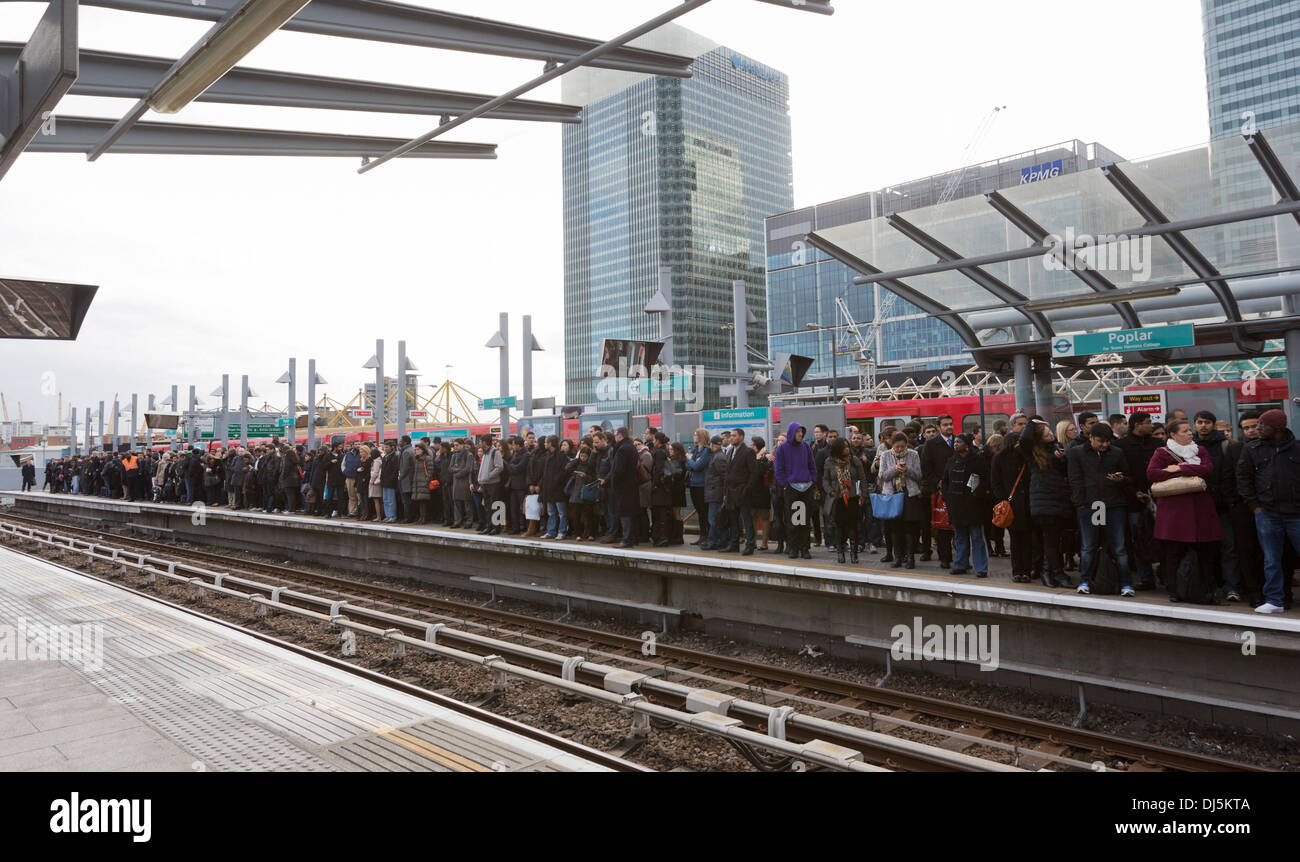 Crowded platform at the Poplar DLR station. Commuters waiting for a train during rush hour. London, England, United Kingdom. - Stock Image