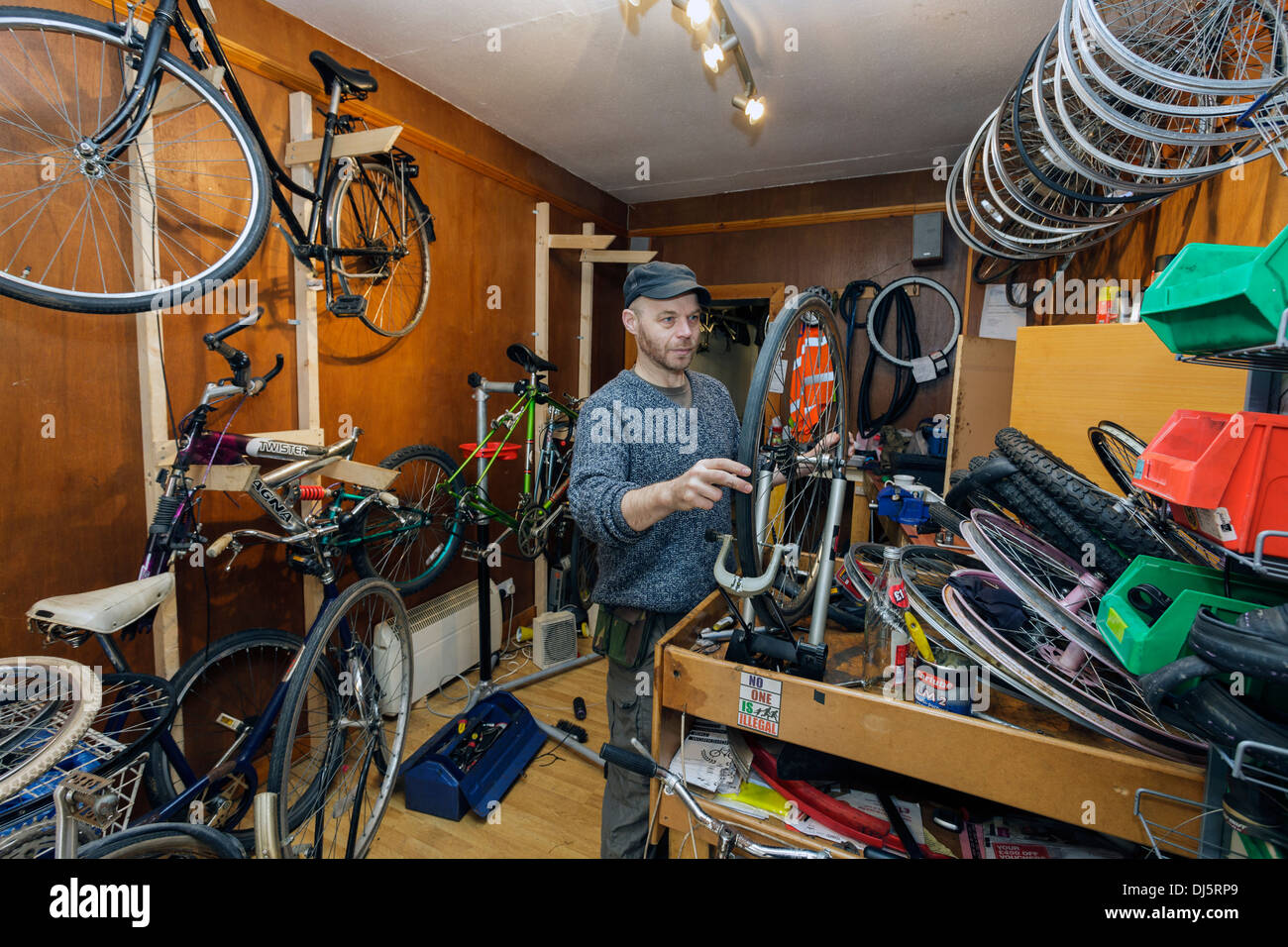 Man repairing bicycles at a workshop in Govan, Glasgow, Scotland, UK - Stock Image