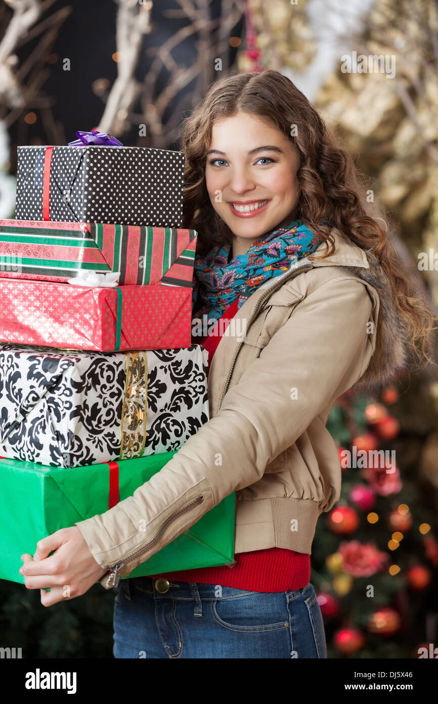 Woman Carrying Stacked Gift Boxes In Christmas Store - Stock Image