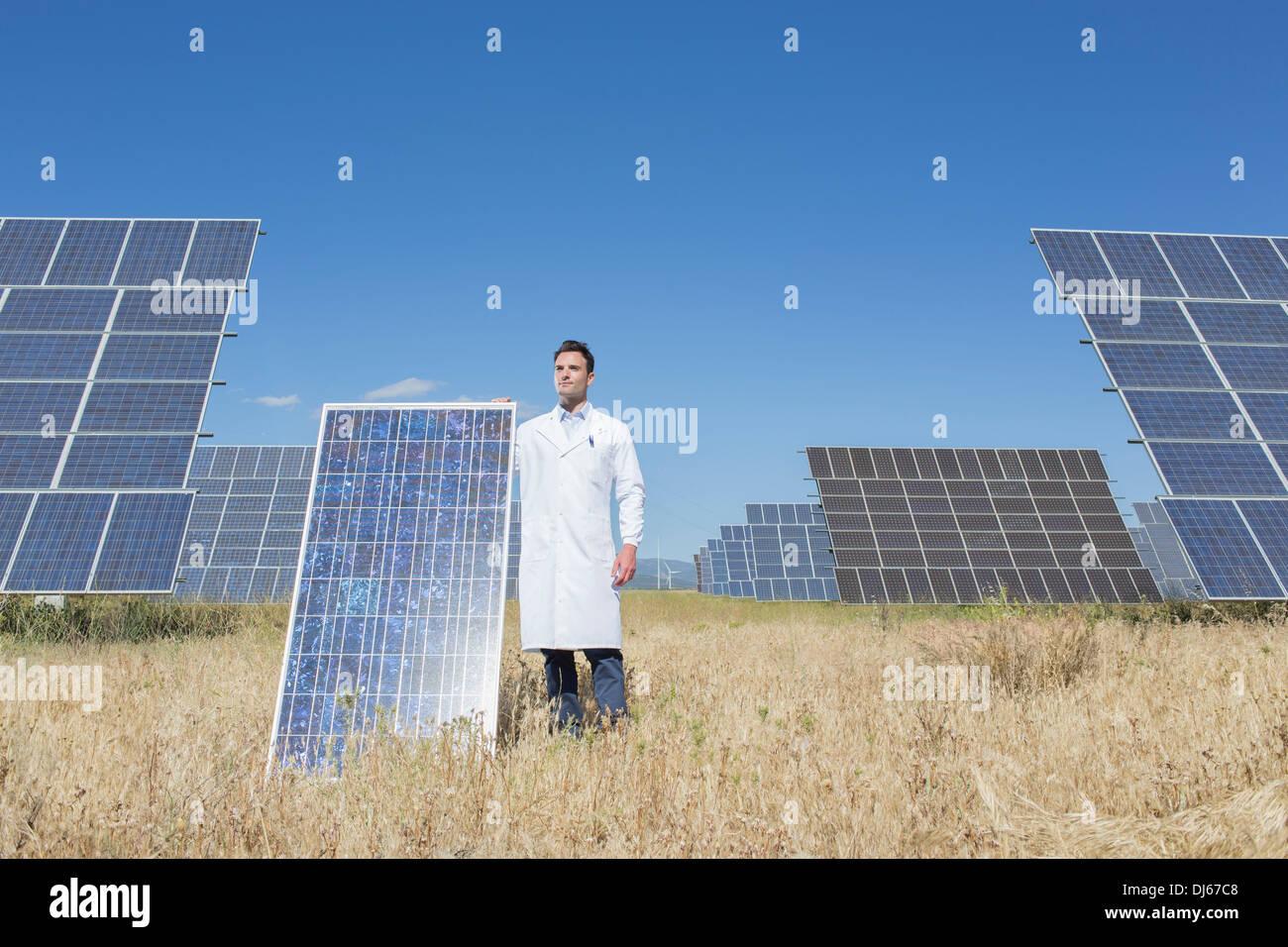 Scientist holding solar panel in rural landscape - Stock Image