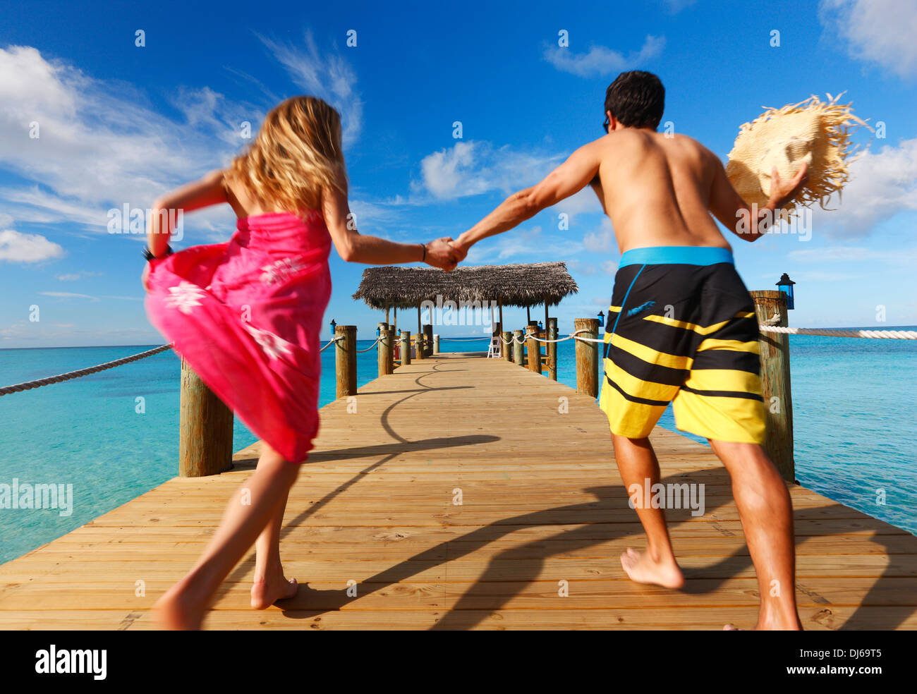 Young couple running on the wooden pier.  Nassau, Bahamas, Caribbean. Stock Photo