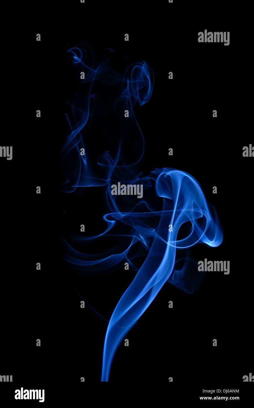 Blue smoke on the black background. Smooth waves of smoke. - Stock Image