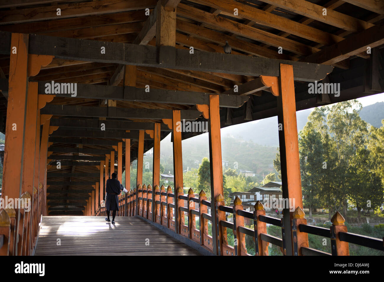 Bhutan, Punakha Dzong, man crossing bridge over Mo Chhu River - Stock Image