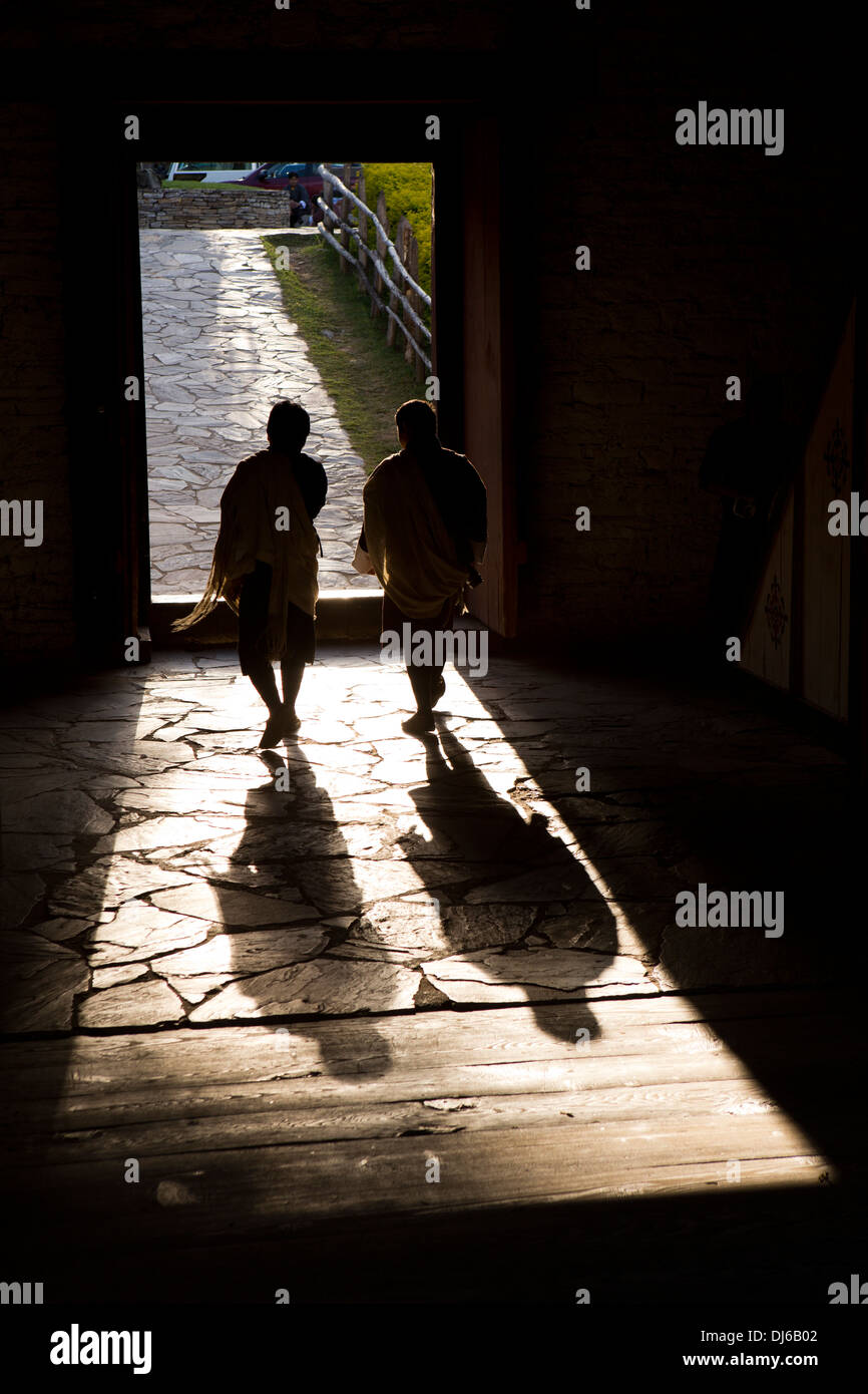 Bhutan, Punakha Dzong, men crossing bridge over Mo Chhu River, silhouette - Stock Image