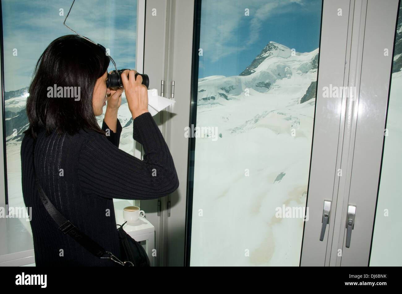 Europe. Switzerland, Canton Bern. Bernese Oberland, Interlaken. Jungfraujoch. using binocular for a closer look to the glacier. - Stock Image