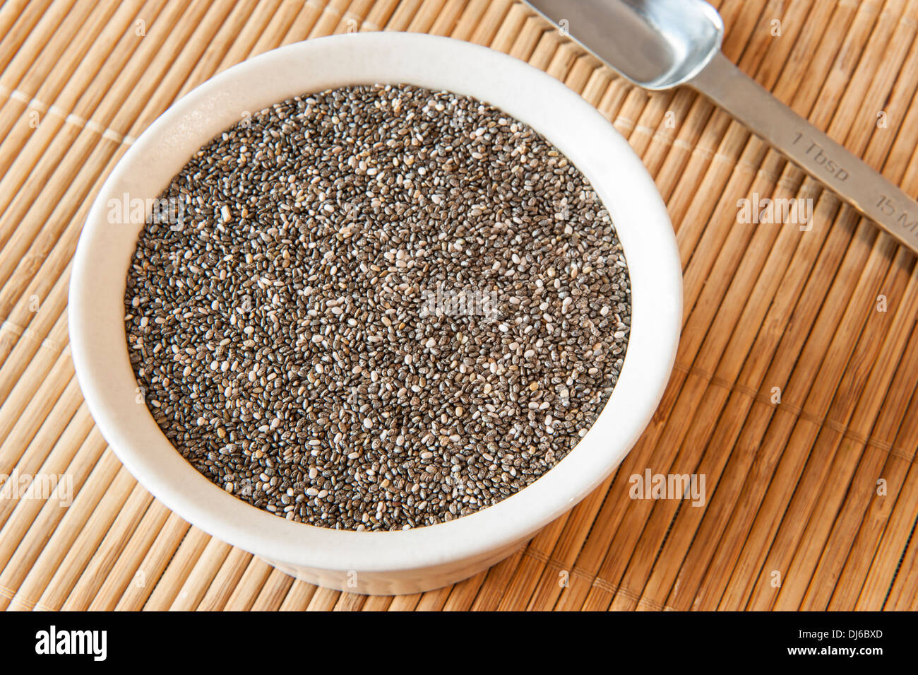 Dish of chia seeds with a measuring spoon on a bamboo mat - Stock Image