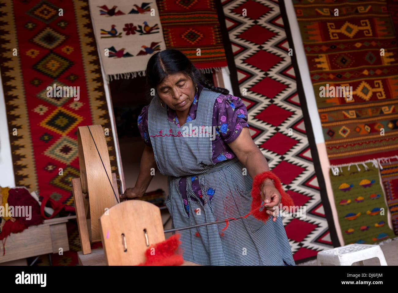 A Zapotec indigenous woman hand spins dyed wool into yarn to be used in weaving traditional carpets in Teotitlan, Mexico. - Stock Image