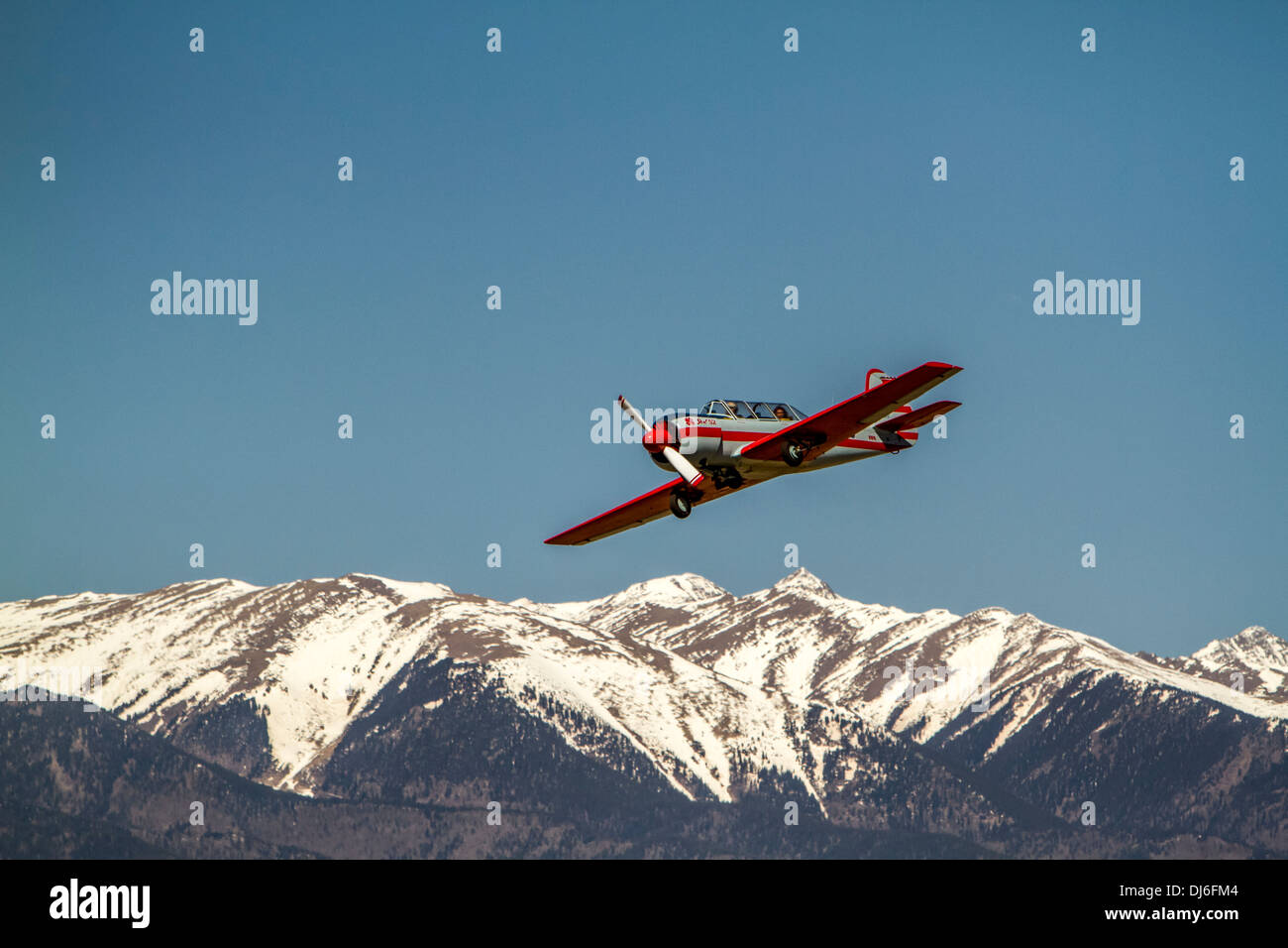 Airplane flying over the mountains. - Stock Image