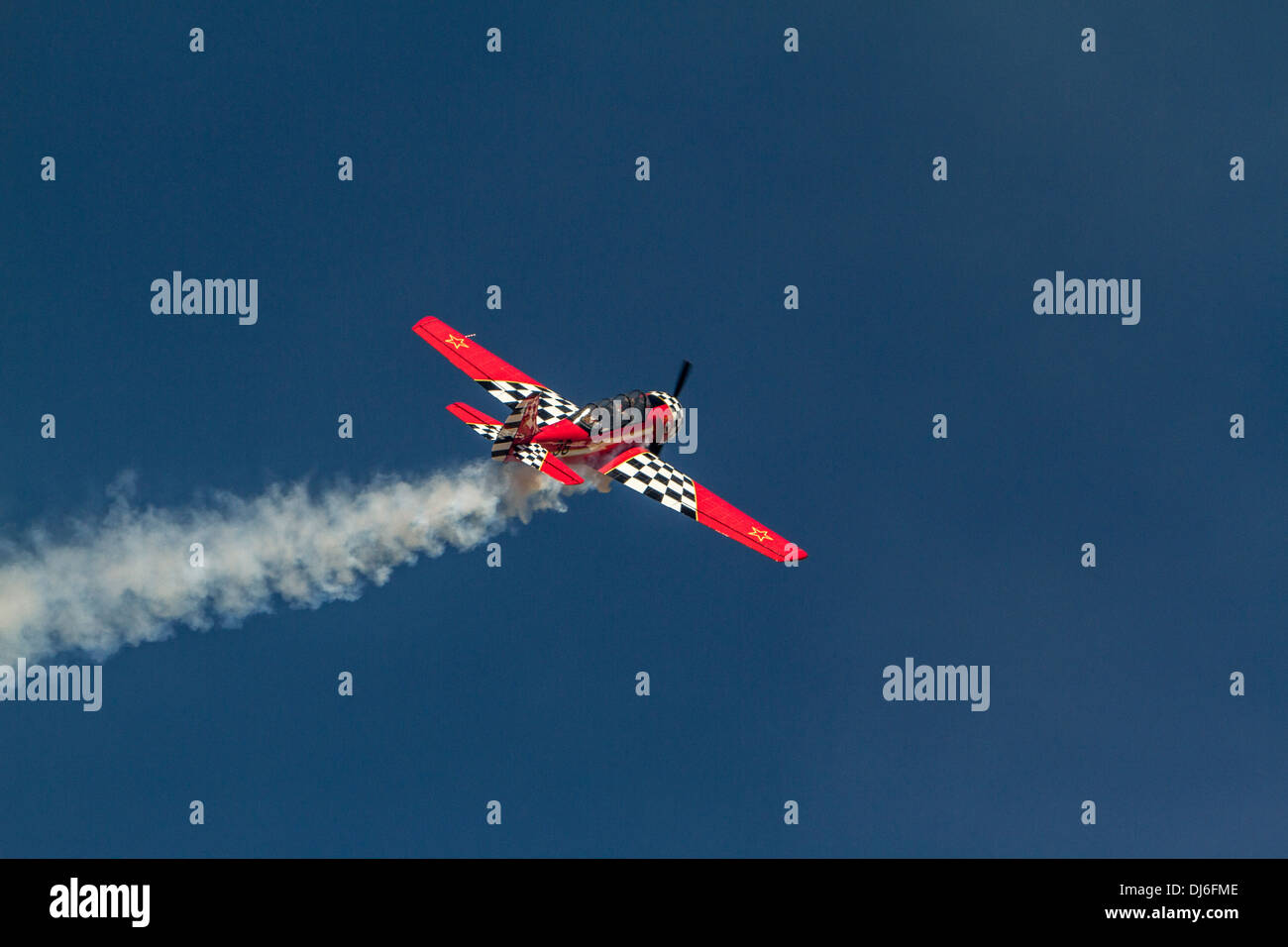 Airplane with Smoke flying on a perfect blue sky. - Stock Image