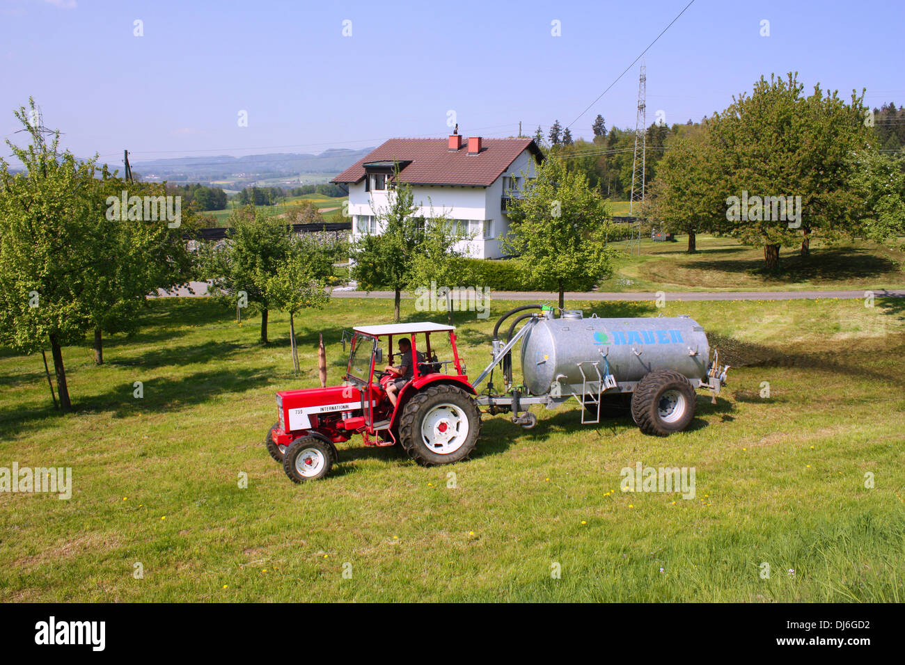 Tractor in green field in Switzerland Stock Photo