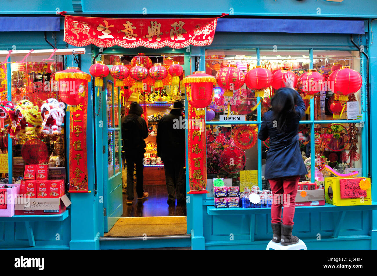 A woman puts up decorations on a shop, in preparation for Chinese new year - Stock Image