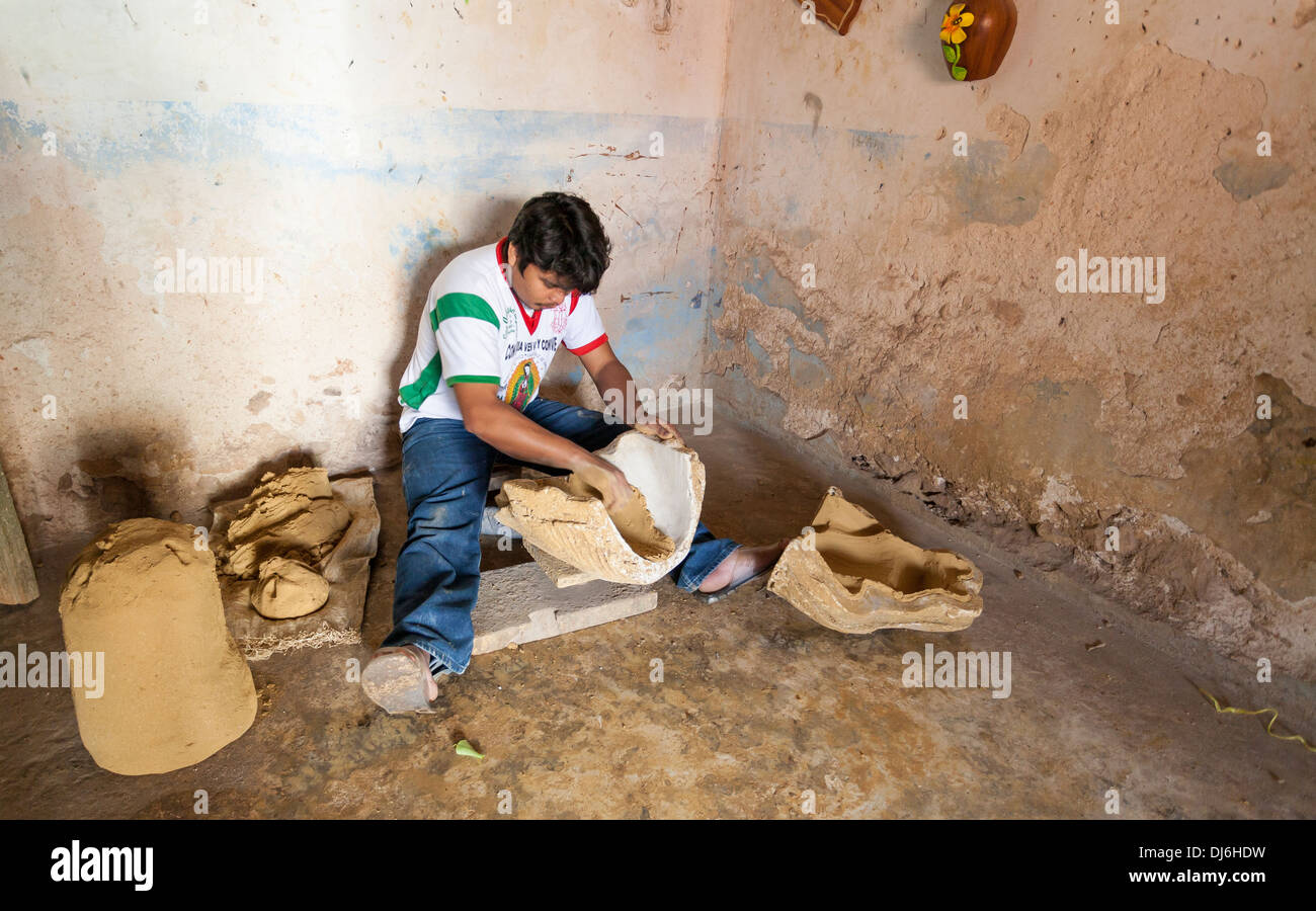Coating the Mold. A potter works in a small concrete room coating the inside of molds to create the large pieces - Stock Image