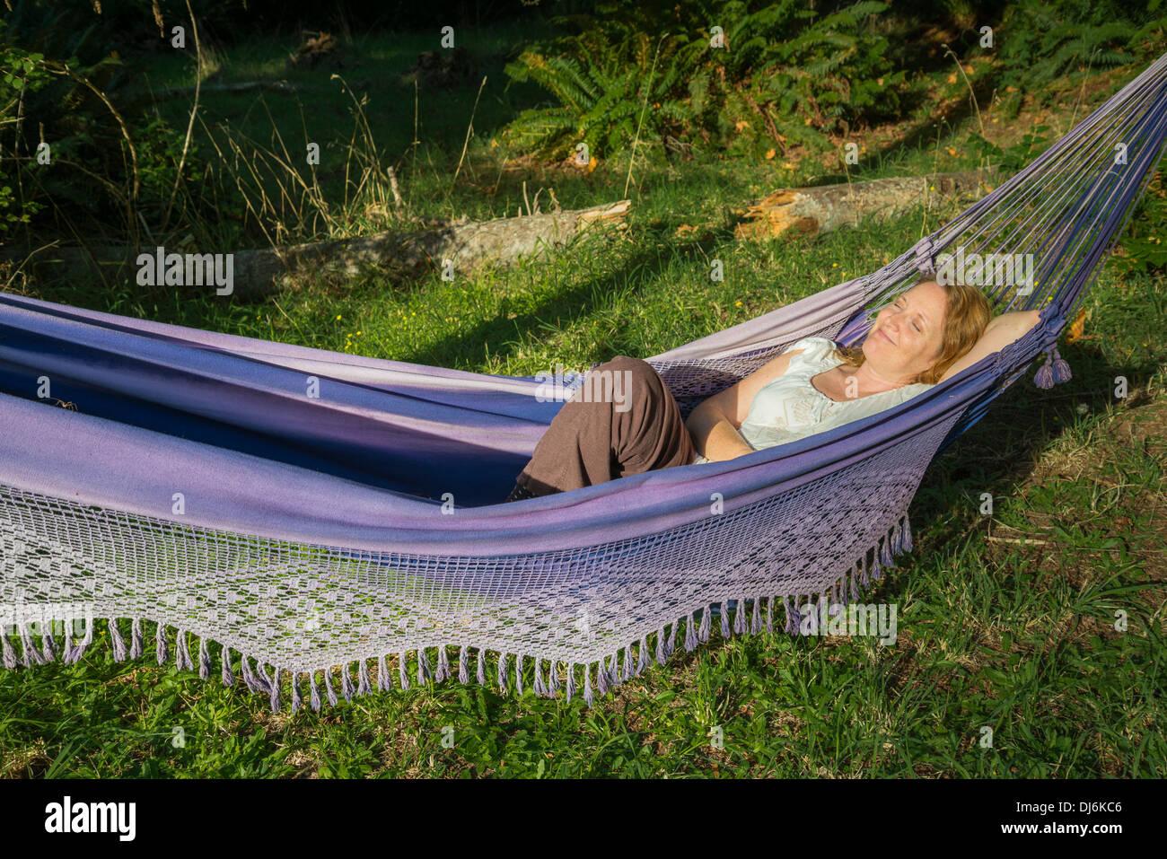 Woman enjoying rest in hammock - Stock Image