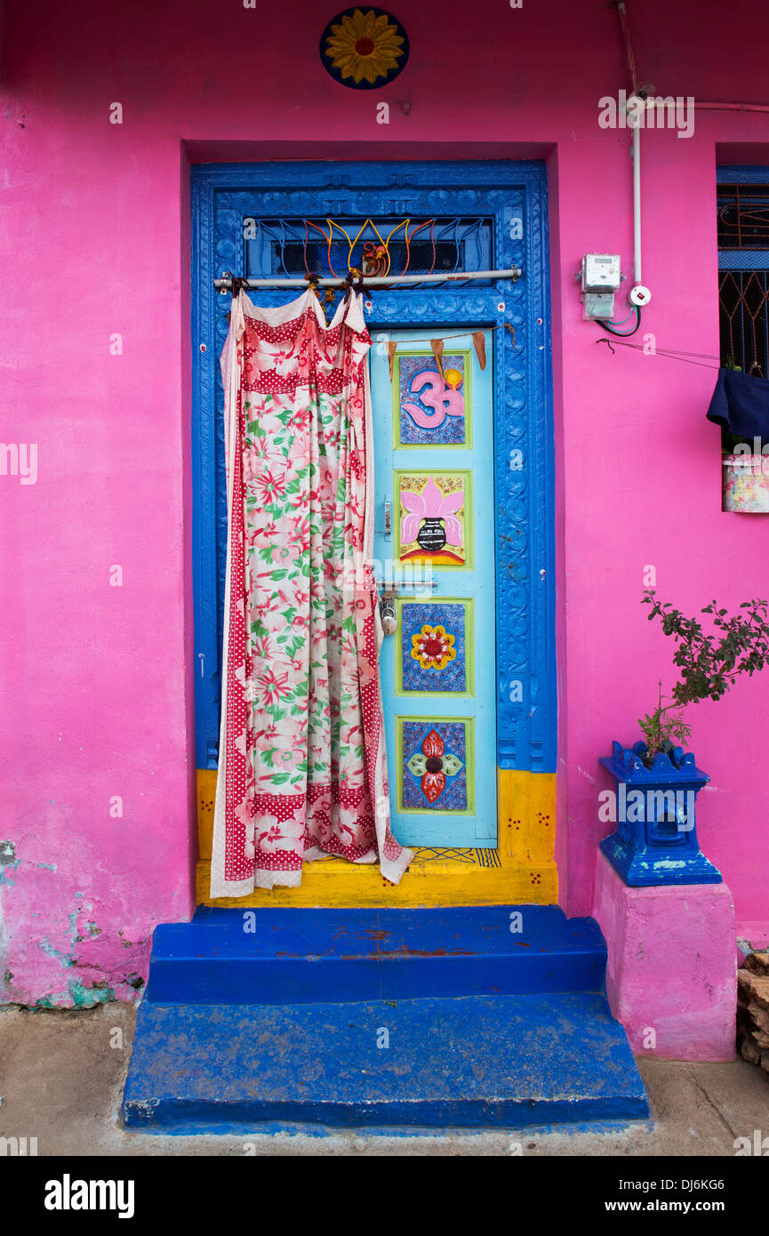 Decorative wooden front door on a blue and pink painted house in an ...
