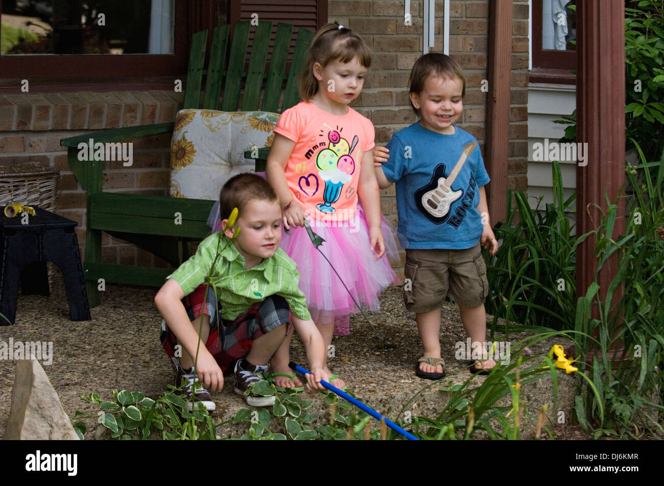 Five Year Old Brother , Three Year Old Sister and Two Year Old Cousin Playing on Porch of Suburban Home - Stock Image