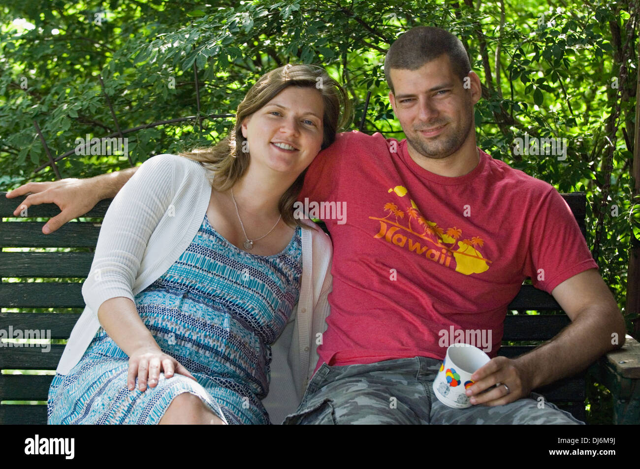 Young Married Couple on Porch Swing - Stock Image