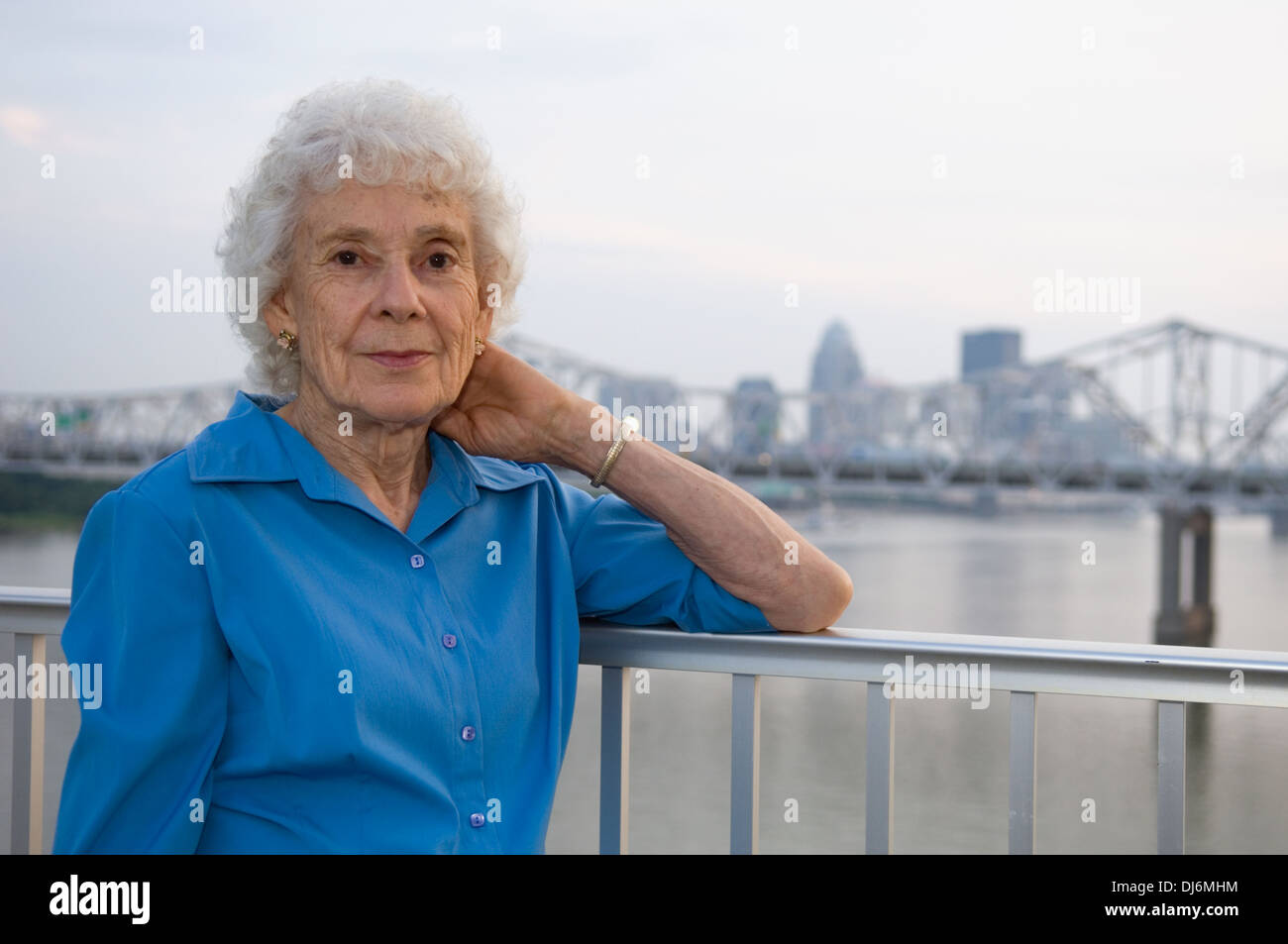 Senior Woman Posing for Photograph on the Big Four Pedestrian Bridge with Louisville Kentucky in the Background - Stock Image