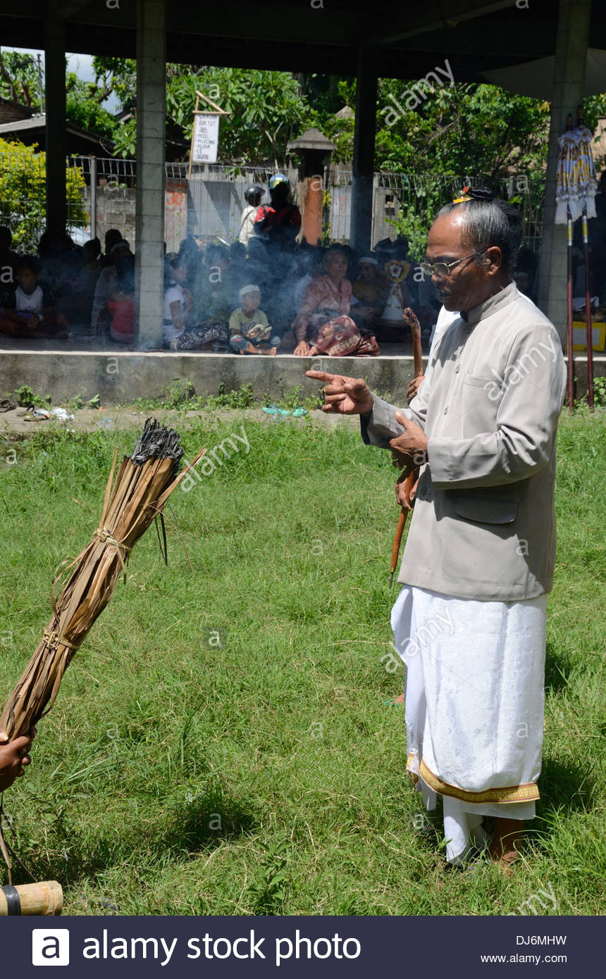 Pedana or Hindu priest blesses  smoking bundle of palm leaves that will be used to set alight  pyre/coffin  Balinese cremation - Stock Image