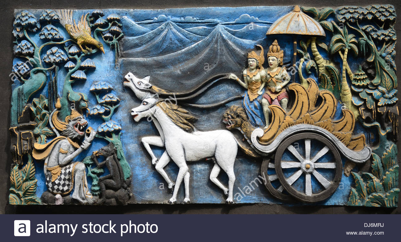 Hindu deities Arjuna and Dewi Sinta stand riding in a chariot drawn by two white horses - Stock Image