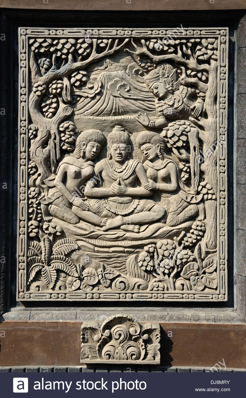 Relief carving panel on wall of Balinese Hindu temple depicting trinity of the three deities Brahma Shiva and Vishnui - Stock Image