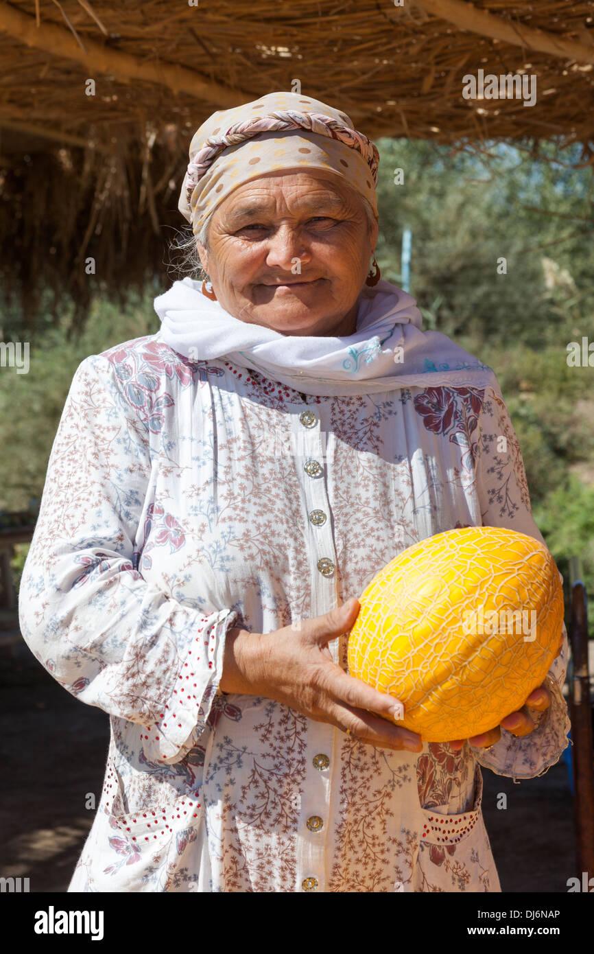 Uzbek woman holding a melon, Shabboz, Beruniy District, near Urgench, Uzbekistan - Stock Image