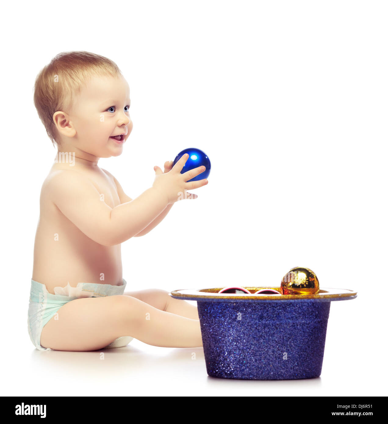 baby playing with christmas balls, isolated on white - Stock Image