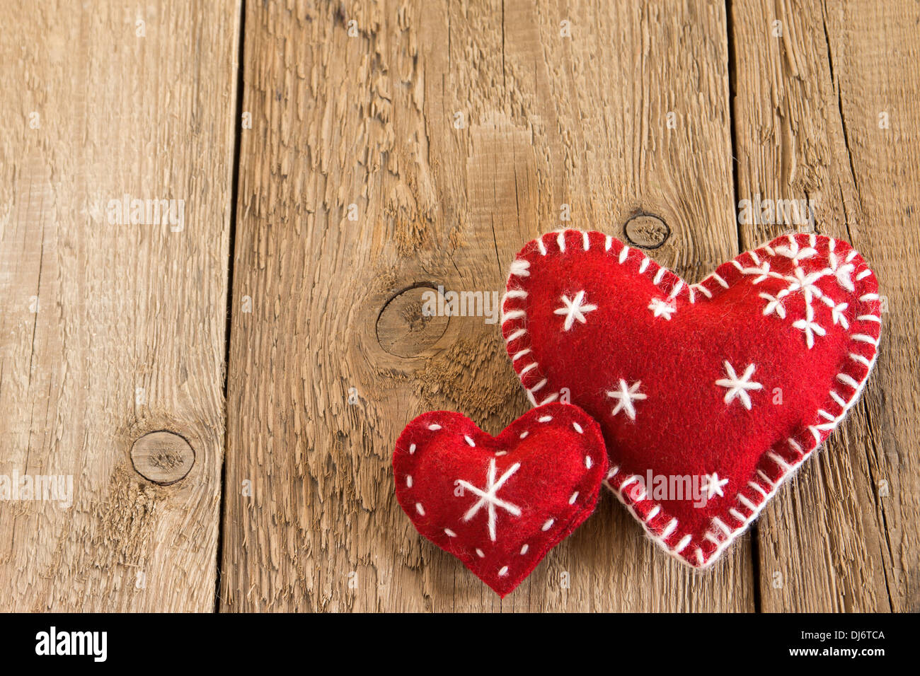 Christmas concept (decoration). Two red handmade hearts over rustic wooden background (texture) close up, horizontal. - Stock Image