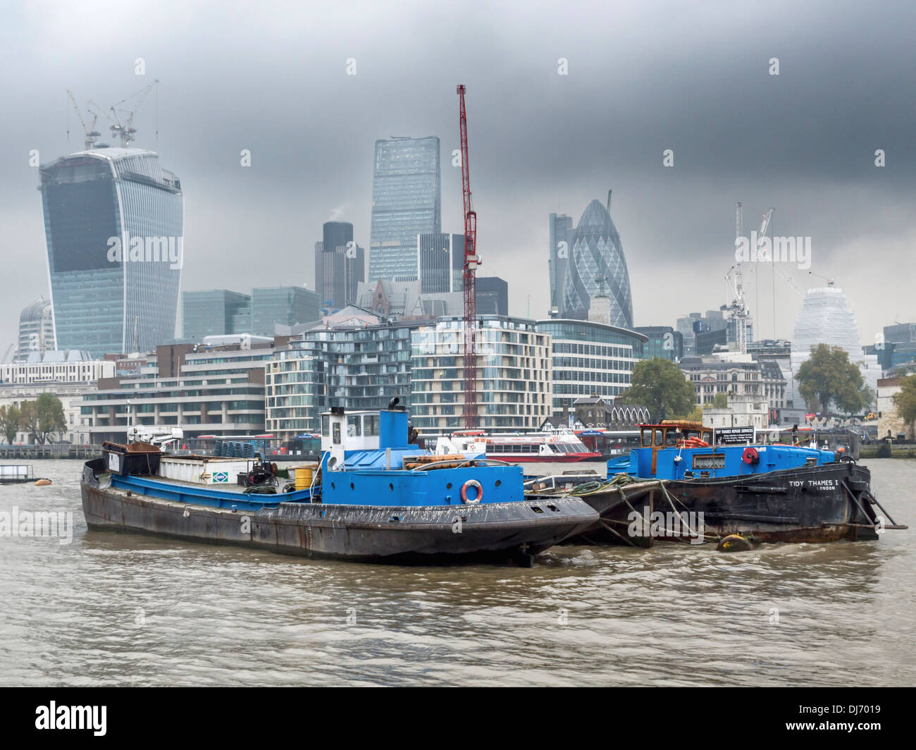 'Tidy Thames' refuse boat in front of modern architecture (nicknamed cucumber and mushroom buildings) of London - Stock Image