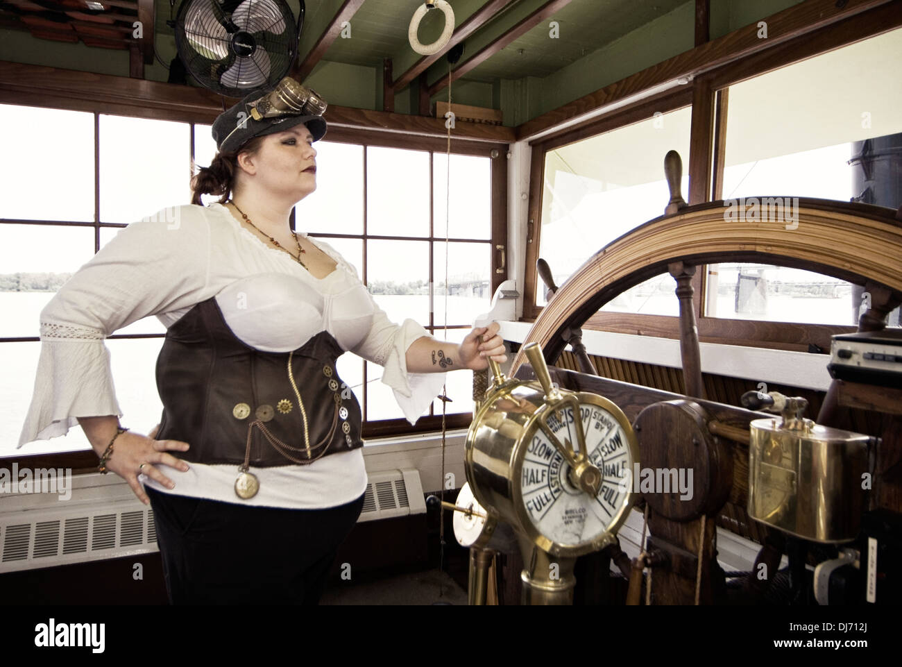 Young Woman Dressed in Steampunk Posing in the Wheelhouse on the Belle of Louisville - Stock Image