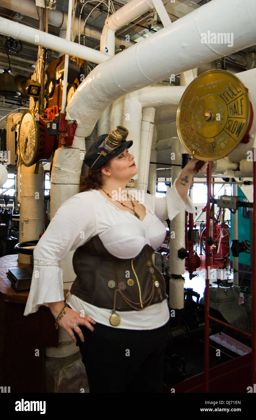 Young Woman Dressed in Steampunk Posing with Engine Room Controls on the Belle of Louisville Stock Photo