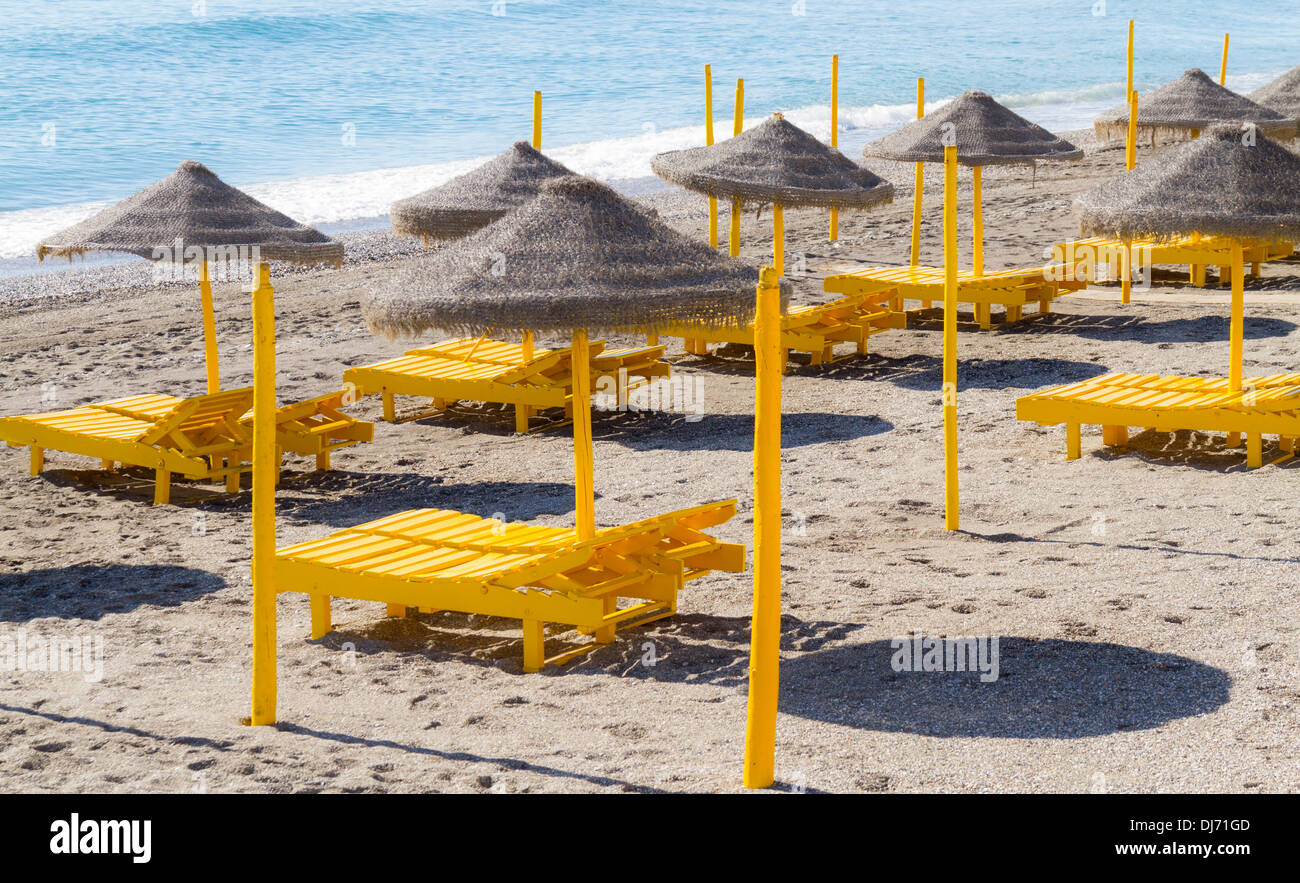 Empty beach loungers on a Spanish beach on a sunny winters day - Stock Image